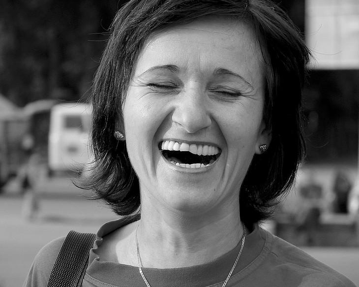 אישה מבוגרת מחייכת עם עיניים עצומות