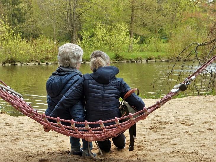 צילום גב של אישה צעירה ואישה מבוגרת יושבות על ערסל מול אגם
