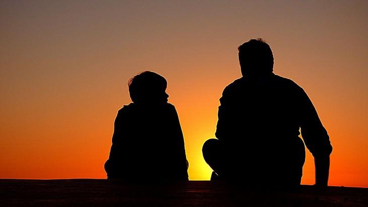 אבא ובן יושבים מול השקיעה