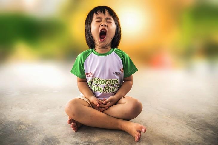 ילדה יושבת בשיכול רגליים ומפהקת