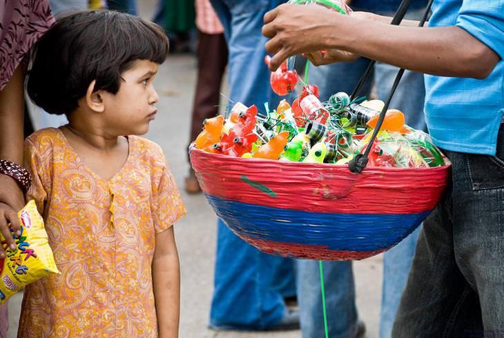 ילדה מסתכלת על סלסלת צעצועים של רוכל
