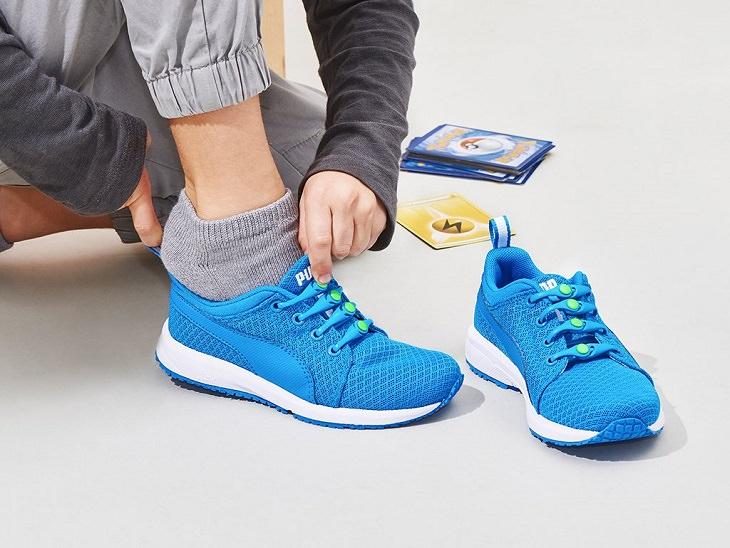 אדם נועל נעלי ספורט עם שרוכי גומיות חכמים