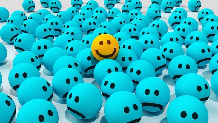 איור של סמיילי שמח בין סמיילים עצובים