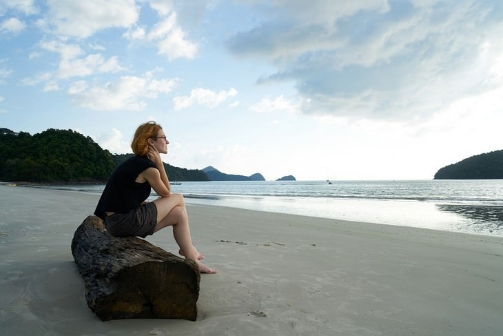 אישה יושבת מול הים