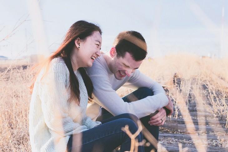 זוג יושב בשדה וצוחק