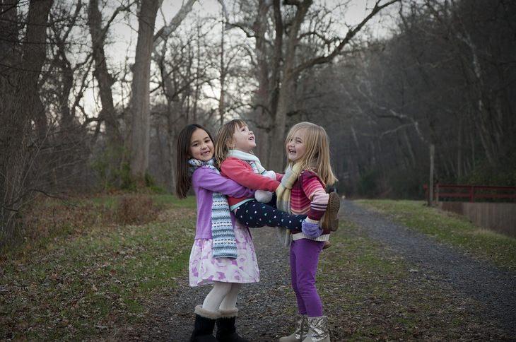 3 ילדות משחקות ליד חורשת עצים
