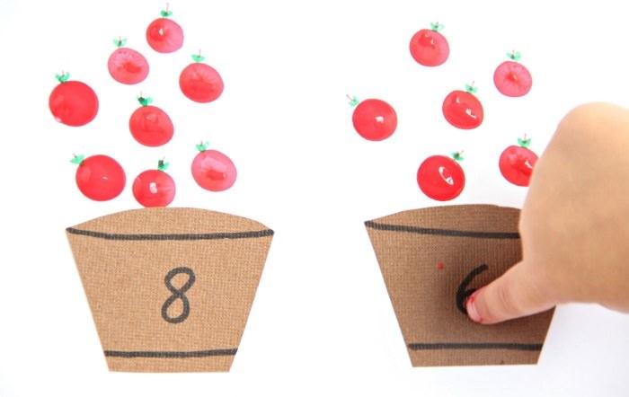 חתיכות קרטון חומות חתוכות בצורת חביות ומעליהן מצוירים תפוחי עץ