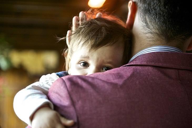 אבא מחזיק ילדה ומרגיע אותה