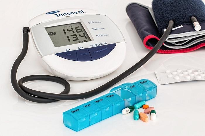 מד לחץ דם וקופסת תרופות עם כדורים ליד מונחת לצידו