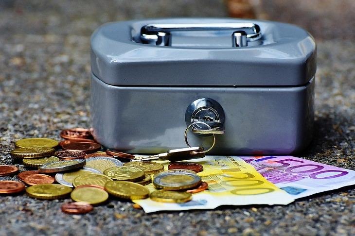 שטרות כסף ומטבעות ליד קופסת פח עם מנעול