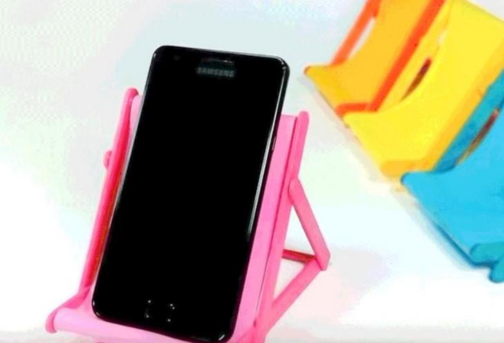 טלפון נייד שוכב על כיסא חוף עשוי מקלות ארטיקים