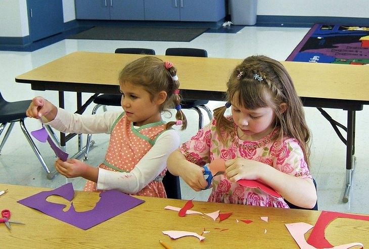 שתי ילדות יושבות בכיתה וגוזרות דפי יצירה