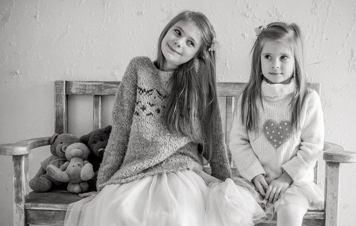שתי ילדות יושבות על ספסל, אחת מפנה ראש וחיוך לשנייה