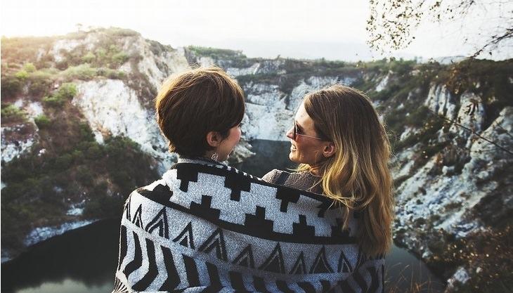 שתי נשים עטופות בשמיכה, מחייכות אחת לשניה, מול נוף הרים