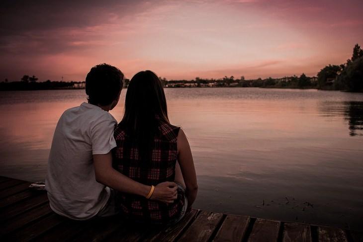 זוג חבוק מול אגם בשקיעה