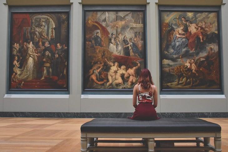 אישה מתבוננת על ציורים במוזיאון, יושבת בגבה למצלמה