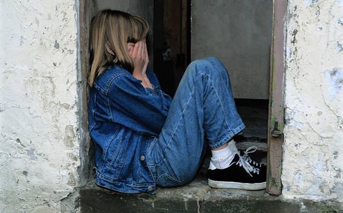 ילד יושב על אדן חלון ומסתיר פניו