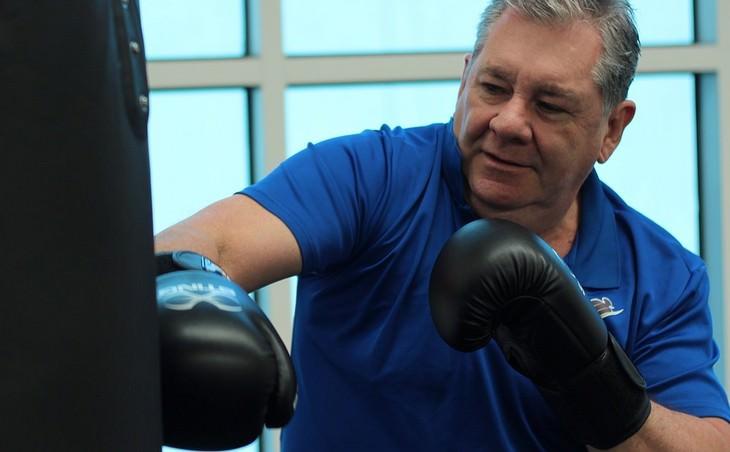 גבר בגיל העמידה מתאגרף מול שק אגרוף
