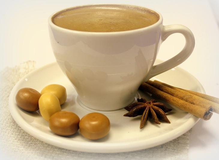 כוס קפה לצד קינמון, כוכב אניס וסוכריות