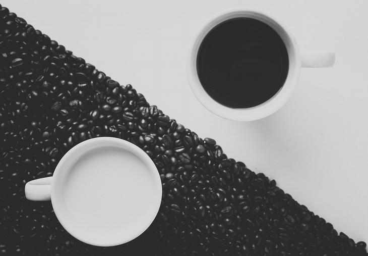 כוס קפה שחור על רקע לבן, לצד כוס עם חלב על פולי קפה