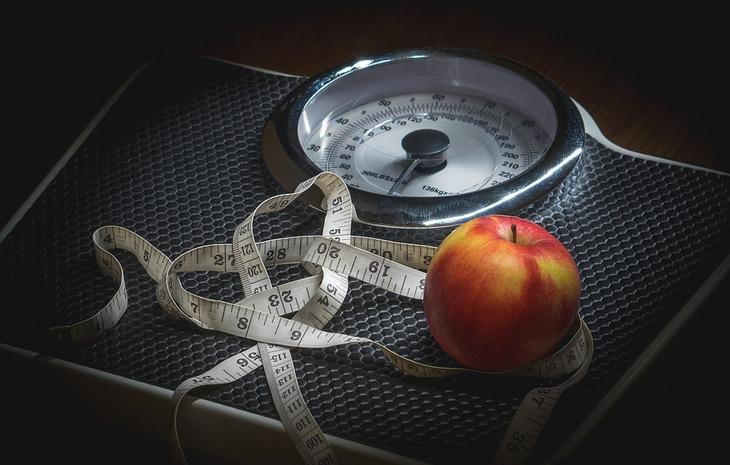 משקל עליו מונחים סרט מדידה ותפוח
