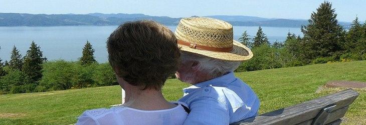זוג מבוגר יושב על ספסל במדשאה מול הים