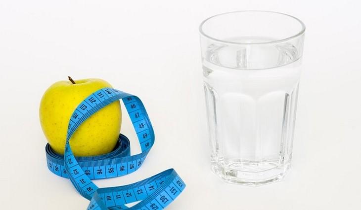 כוס מים מונחת ליד תפוח שעטוף בסרט מדידה