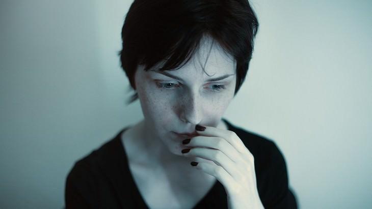 אישה עם מבט חרד מחזיקה ביד את שפתיה