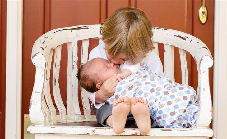 ילדה מחבקת ומנשקת את אחיה התינוק