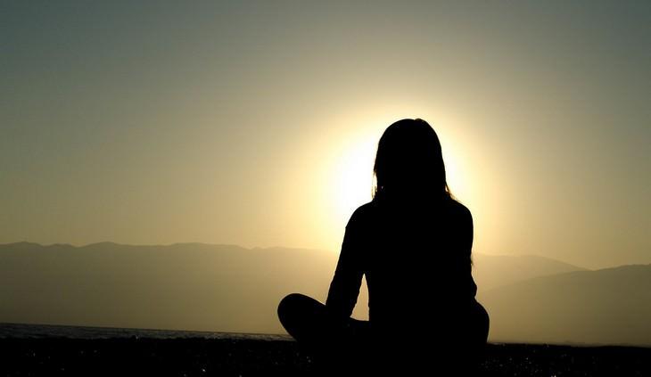אישה יושבת מול שקיעה
