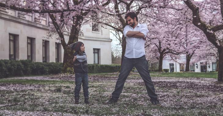 אב ובן משלבים ידיים בביטחון ומסתכלים אחד על השני, תחת עצים פרחוניים