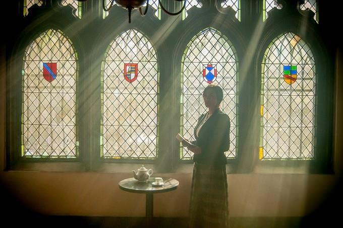 אישה עומדת בתוך מבנה עם חלונות זכוכית מוארים