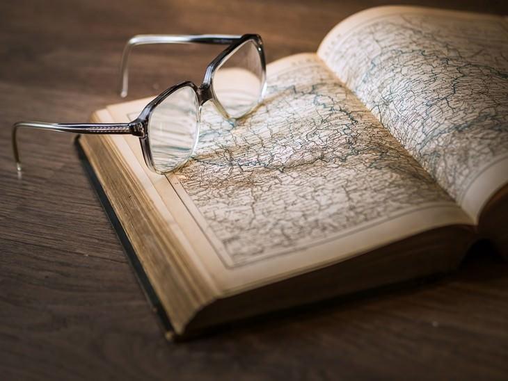 ספר פתוח בעמוד עם איור של מפה עם משקפיים עליו