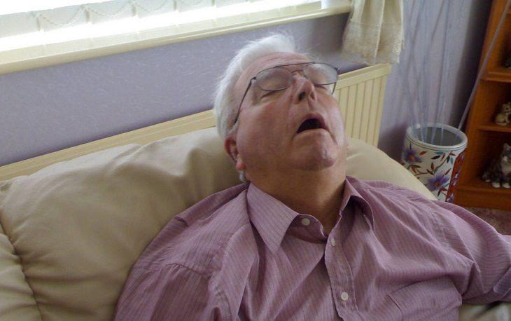 גבר ישן על ספה בפה פתוח