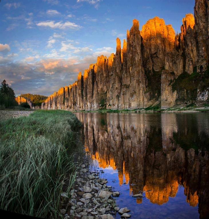 נהר עובר לצד צוקים, שקצותיהם צבועים בזהב