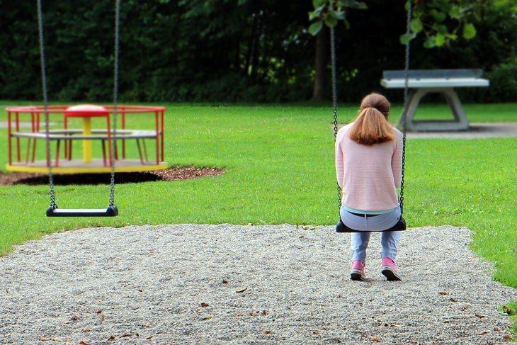 אישה יושבת על נדנדה בגן משחקים, בגבה למצלמה