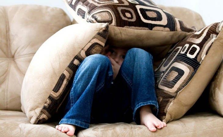 ילד קטן מסתתר בתוך כריות ספה