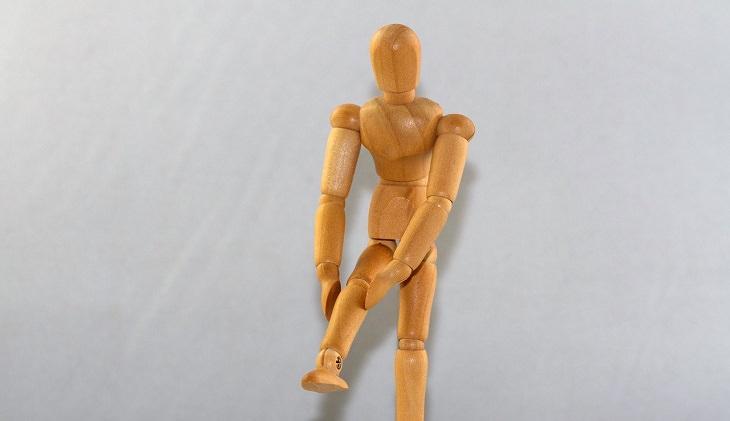 בובת עץ בדמות אדם מוצבת בתנוחה שבה היא תופסת את רגלה