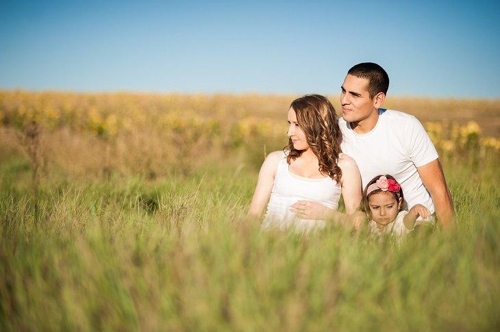 זוג יושב בשדה עם ילדתו