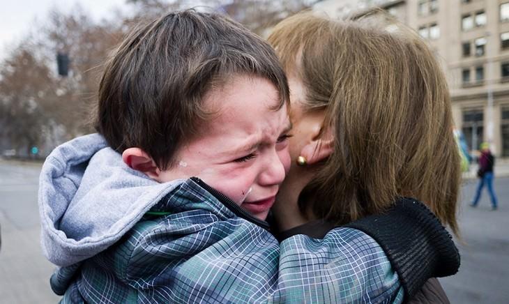 ילד בוכה מחבק אישה