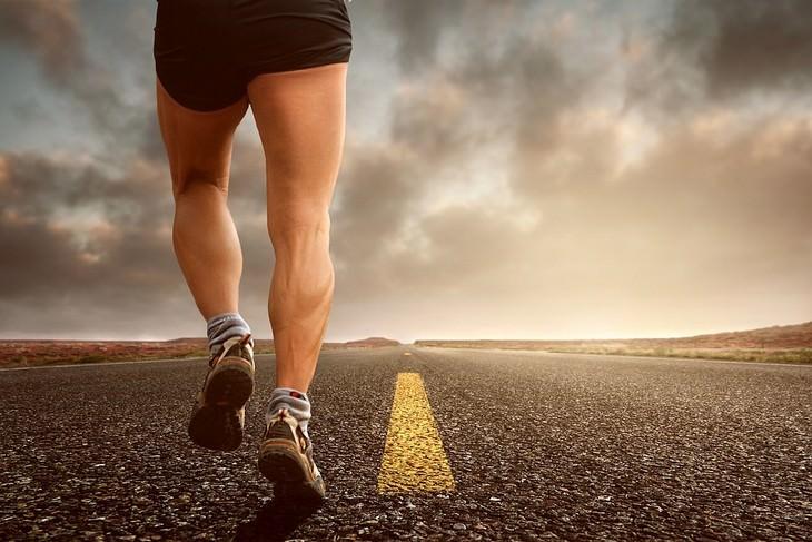 איש עם רגליים שריריות רץ על כביש