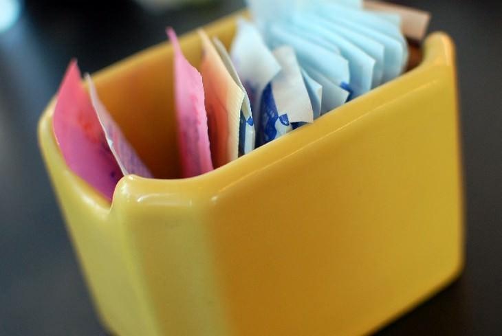 כלי קטן עם שקיקי נייר של ממתיקים מלאכותיים