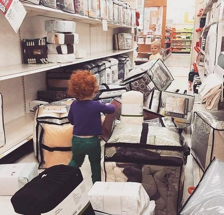 פעוט עומד בחלק של המצעים בחנות עם מצעים מפוזרים סביבו