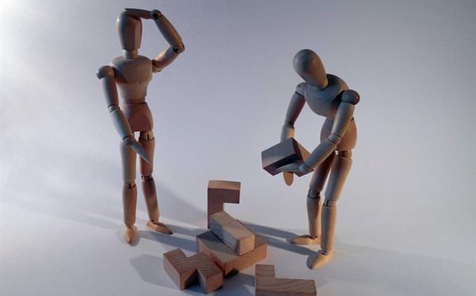פסלי עץ זעירים בונים בלבני משחק