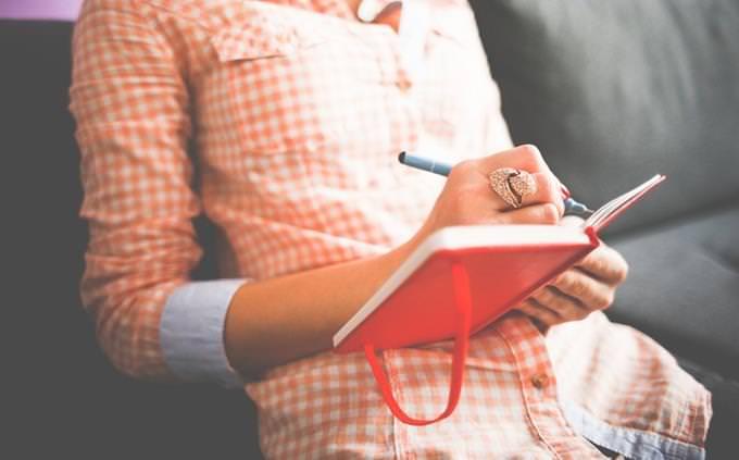 אישה יושבת וכותבת ביומן