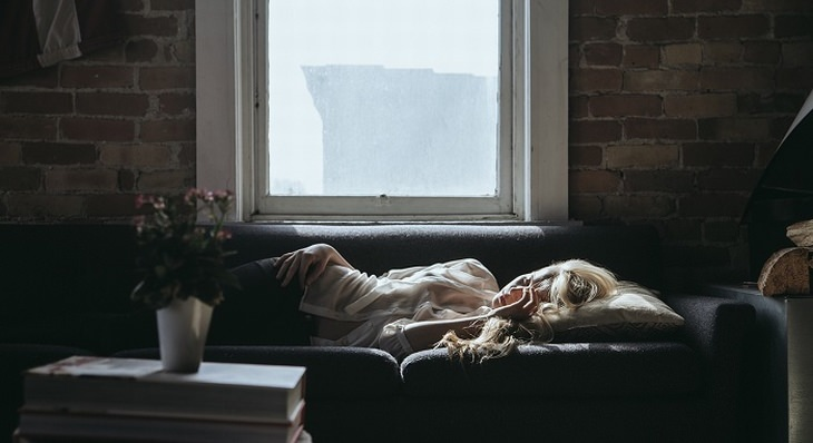 אישה ישנה מתחת לחלון בבית שעשוי מלבנים