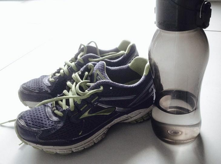 בקבוק מים מונח ליד נעלי ספורט