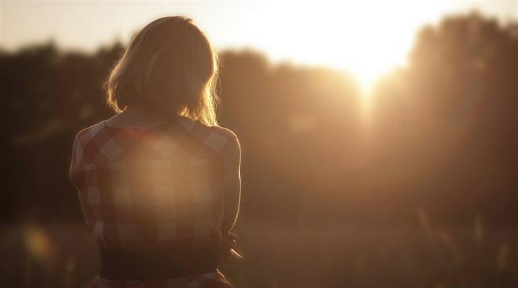 אישה עומדת מול השמש השוקעת בחורשה