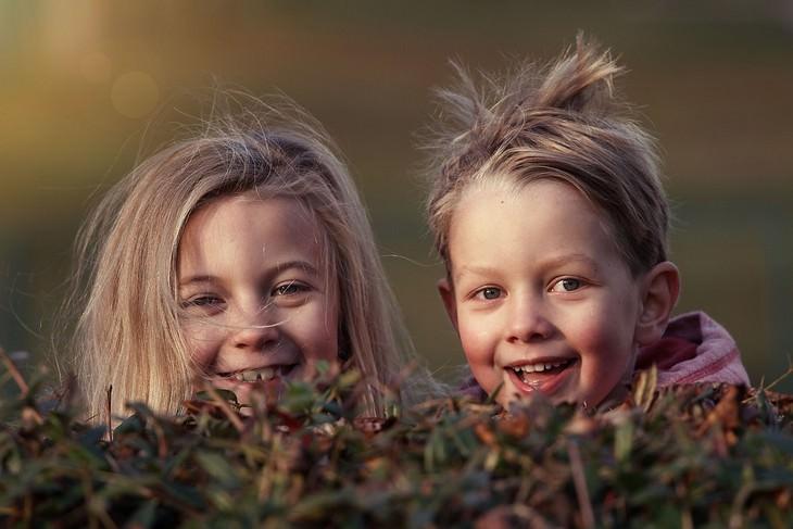 שני ילדים מאחורי שיח