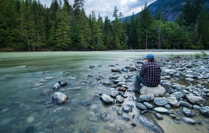 גבר יושב מול אגם ועצים